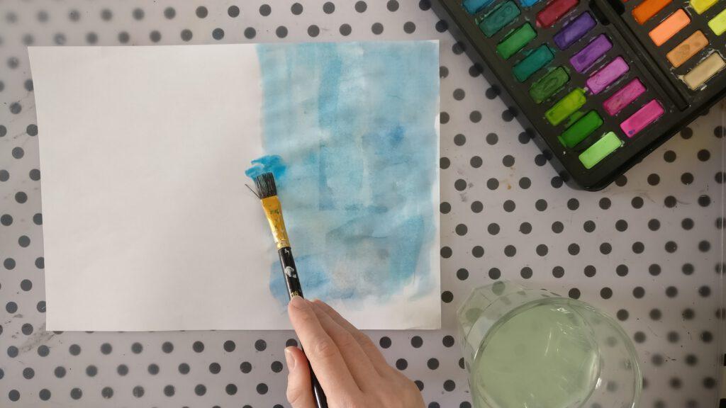 Das Papier mit Wasserfarbe bemalen