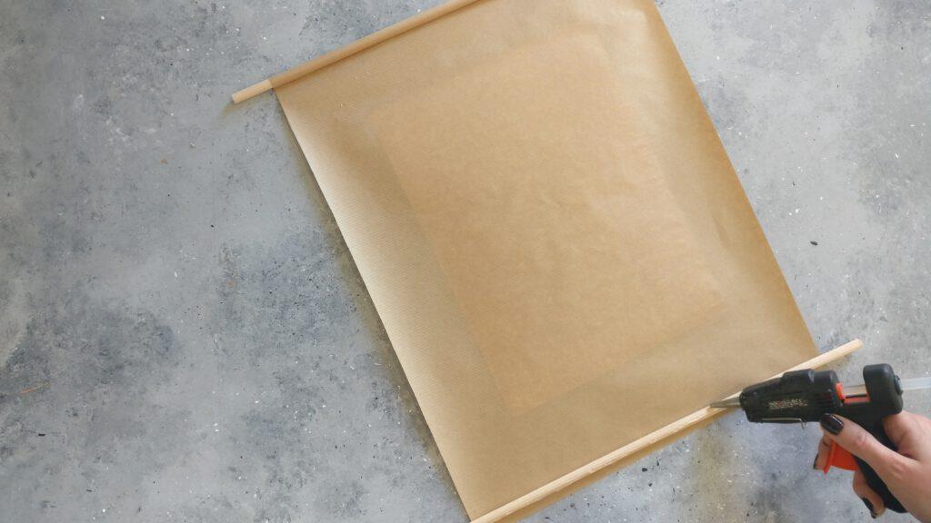 Die Holzstäbe auf das Papier kleben