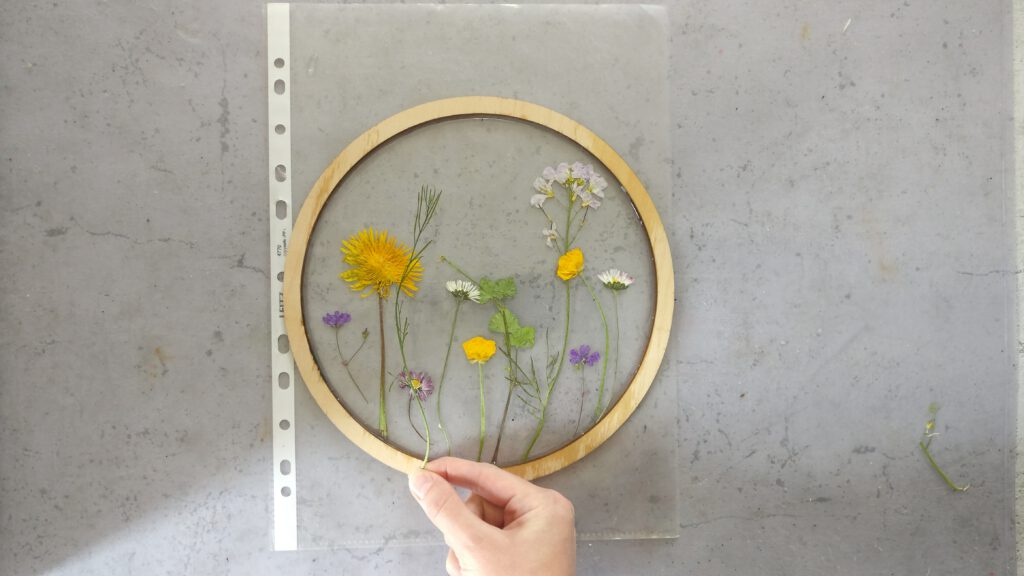 DIY Resin Bild im Botanical Stil: Die gepressten Blumen auf der ersten schicht Resin verteilen.