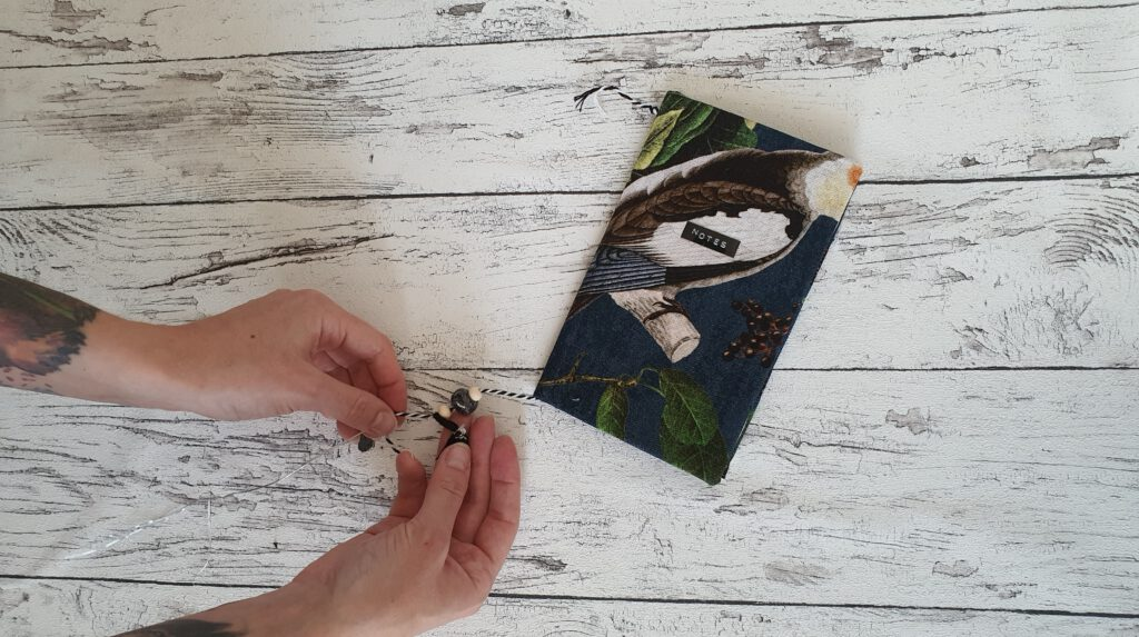 DIY Notizheft Schritt 8: Lesezeichen aus Garn und Perlen anbringen